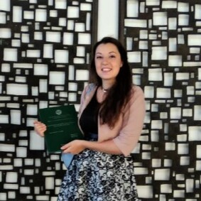 Photo of a woman holding a certificate and smiling at the camera.