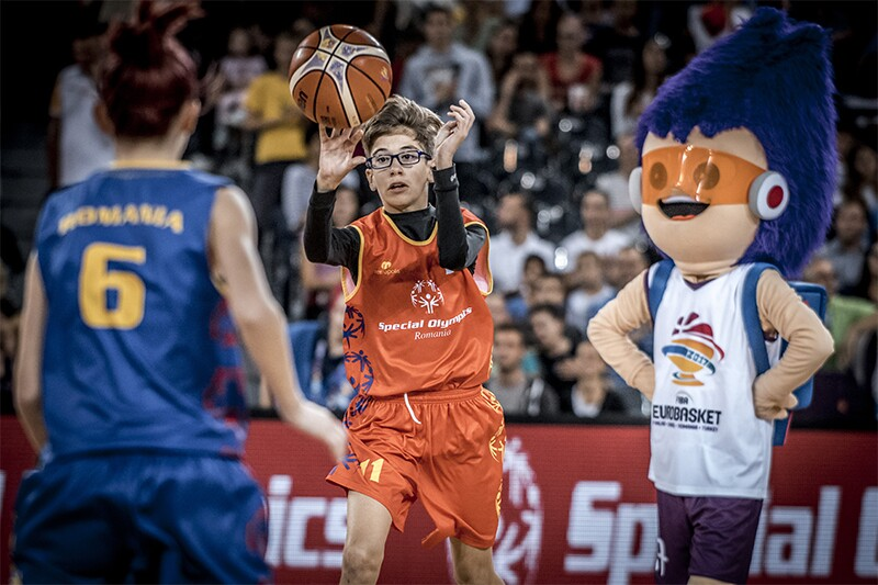 Young male Romanian player in an orange uniform catching the basketball. The 2017 Eurobasket mascot is in the middle ground. A girl is in the foreground wearing a blue uniform with the number 6 on her back. An audience is watching the action in the background.