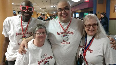 Hankins (left) posing for a picture in a bowling alley with mentor Debra and her son Chris, pre-COVID-19.