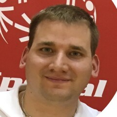 Adam Hammer smiling in front of a backdrop of the Special Olympics logo.