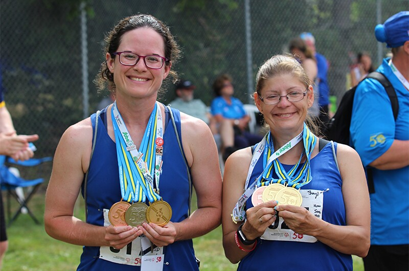 Ashley Adie standing next to another athlete and both are showing off their medals.