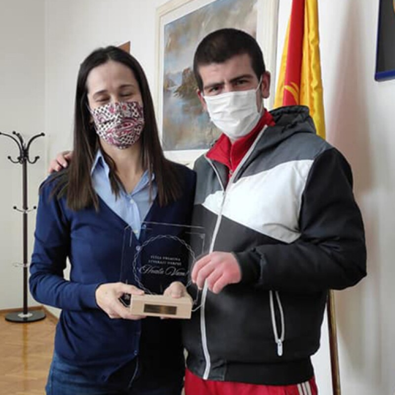 A young woman standing next to a young boy holding an award.