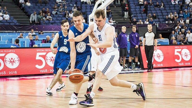 Three male athlete players on the court; two athletes in blue uniforms with one dribbling the ball. A third athlete in a white uniform is trying to steel the ball. and one . Officials and an audience are in the background.