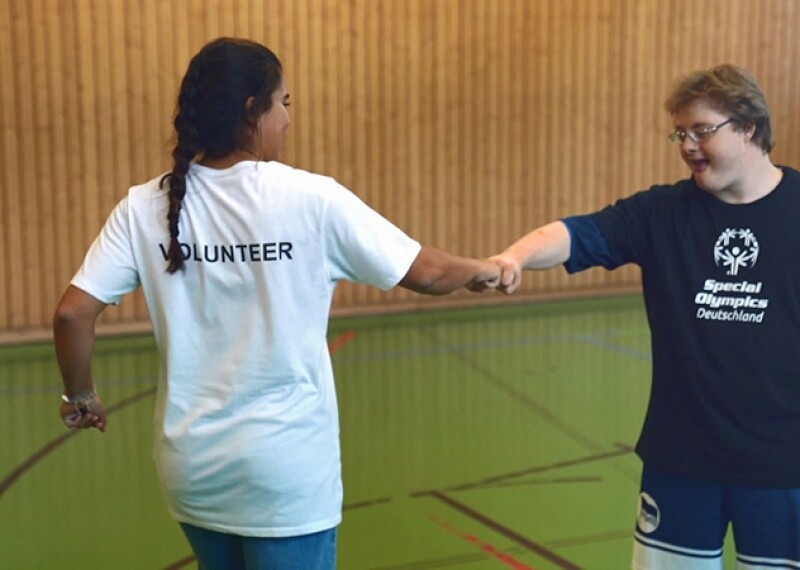 An athlete and volunteer fistbumping on the court.