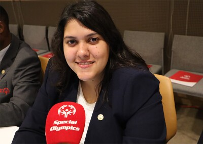 Emanuelle de Souza sitting in front of a microphone.