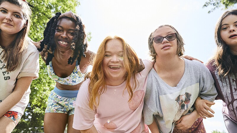 Five young women smile and bend down towards the camera with trees and sky behind them.
