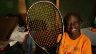 Girl sitting in an orange t-shirt holding a tennis racquet smiling for a photo.