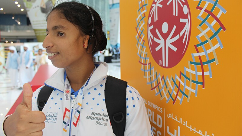 A young woman standing in front of the Athletes Chill Out sign at the 2019 World Games giving a thumbs up and showing off her new hearing aid.