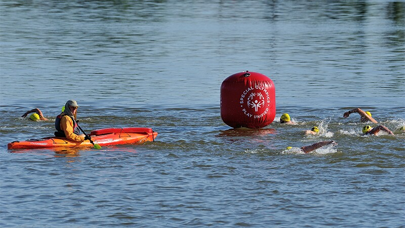 Lifeboats patrol the river and the safety of athletes in the open water as the swimmers round a Special Olympics Play Unified themed Buoy.