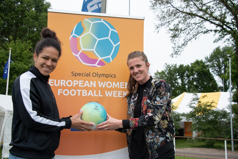 Two women stand holding a ball in front of an orange Special Olympics European Women's Football Week banner.