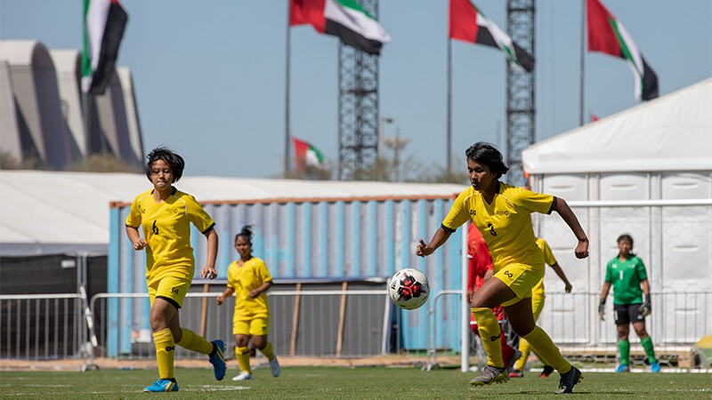 Four female players on the field, one is kicking the ball and a keeper is seen in the background.
