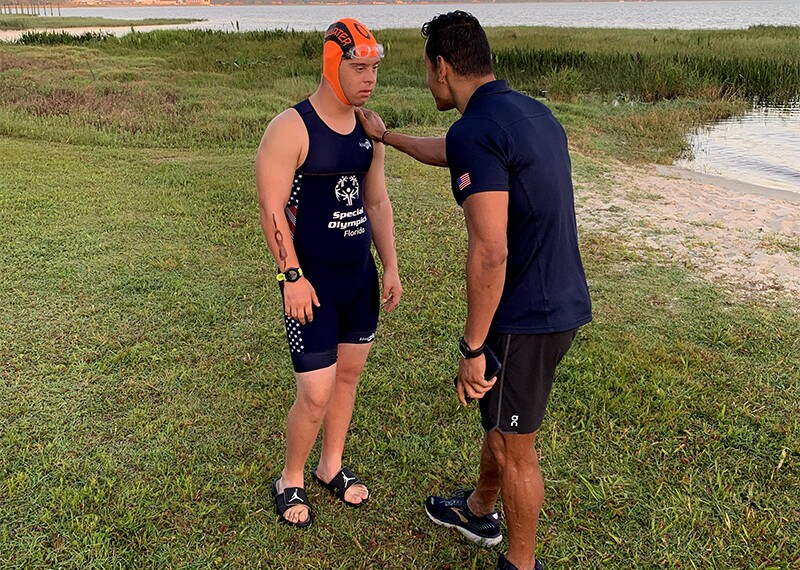 Chris Nikic with a coach on the banks of the water before his swim.