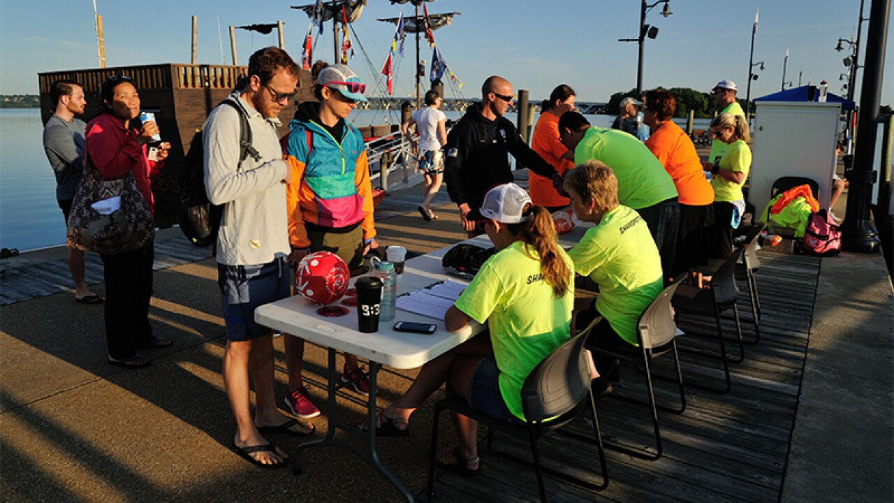 Attendees registering for the event at a table with volunteers on the dock.