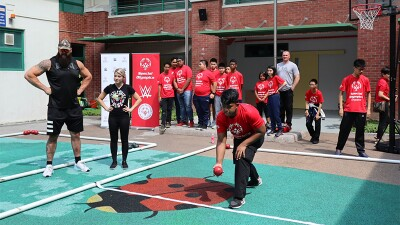 WWE pro stars and Singapore athletes play Bocce on a court outside.