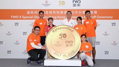 FWD group representatives and Special Olympics Hong Kong representatives pose around a large gold colored medallion in front of a back drop sponsored by FWD and Special Olympics Hong Kong that reads: FWD X Special Olympics Hong Kong Partnership Kick-off Ceremony