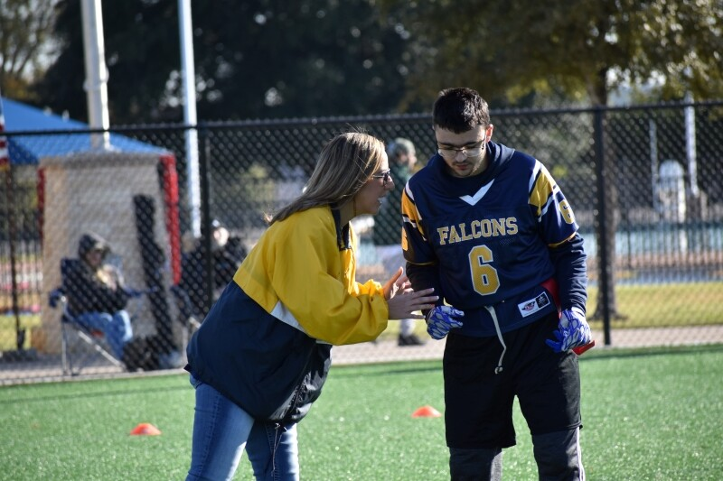 A Special Olympics coach talks to a flag football athlete.