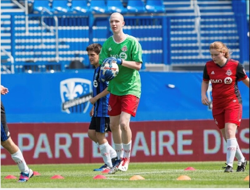 A Special Olympics athlete wears a green soccer jersey and holds a soccer ball in his hands.