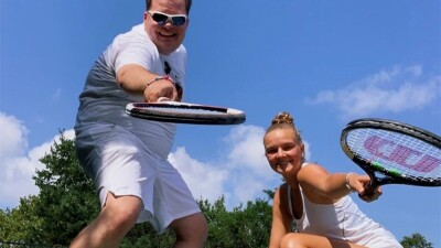 Two tennis players smile and playfully point their tennis rackets towards the camera.