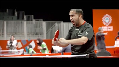 Athlete cheering his victory. other athletes are in the background playing table tennis.