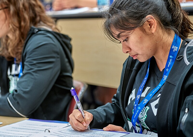 A female student sitting in class working on a project. Another female student can be seen in the background doing the same thing.