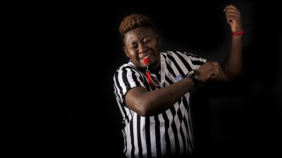 Jimmy with a whistle in his mouth, wearing a ref's shirt and dancing.