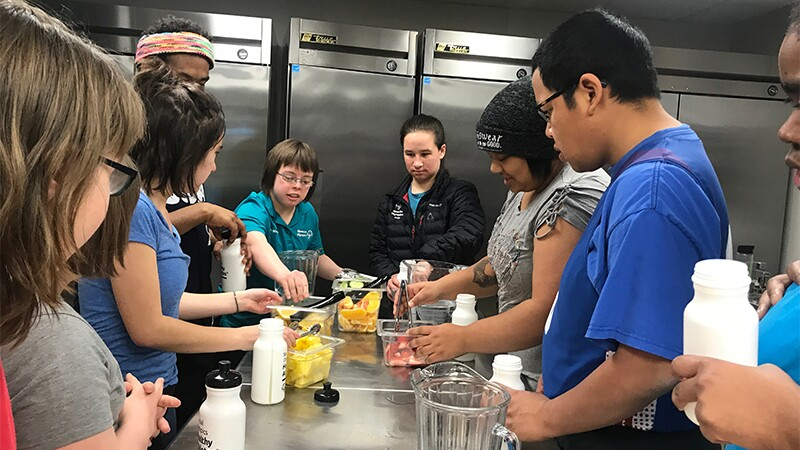 An athlete instructs others that are observing in the chef's kitchen how to eat healthy.