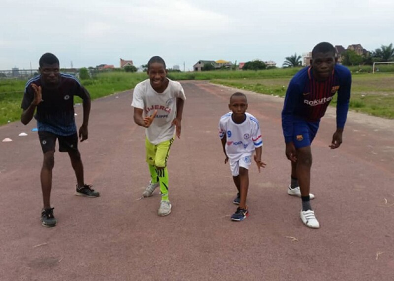 Four young men preparing to race down a track.