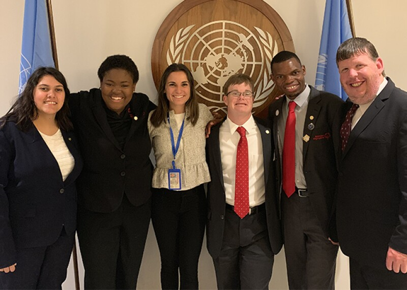 Six people at the U.N. Standing in front of the U.N. insignia.