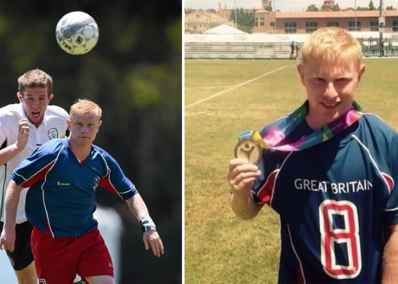 A man runs at the soccer ball. He is wearing a blue and red uniform. A player from a different team runs after the ball behind him.   A Special Olympics Great Britain stands on a football field showcasing his gold medal.