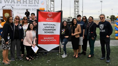 School representatives and unified teams standing by a national unified champion school banner.