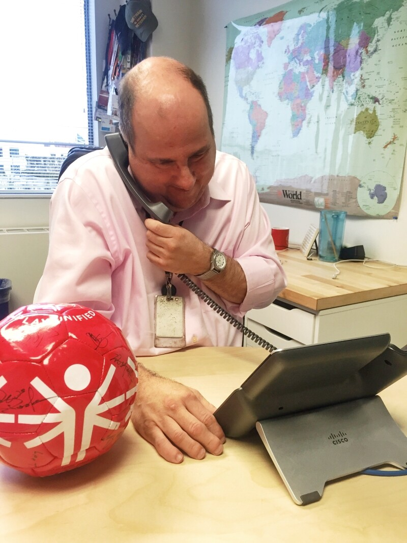 A Special Olympics athlete answers the phone in an office.
