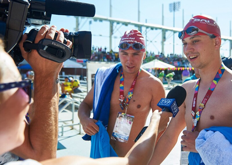 Two men in swimming caps holding towels face a camera and speak to a woman holding a microphone.