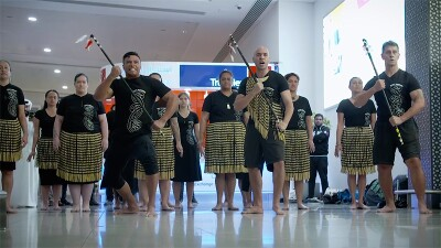 New Zealand dancers performing in front of a group of athletes at the airport.