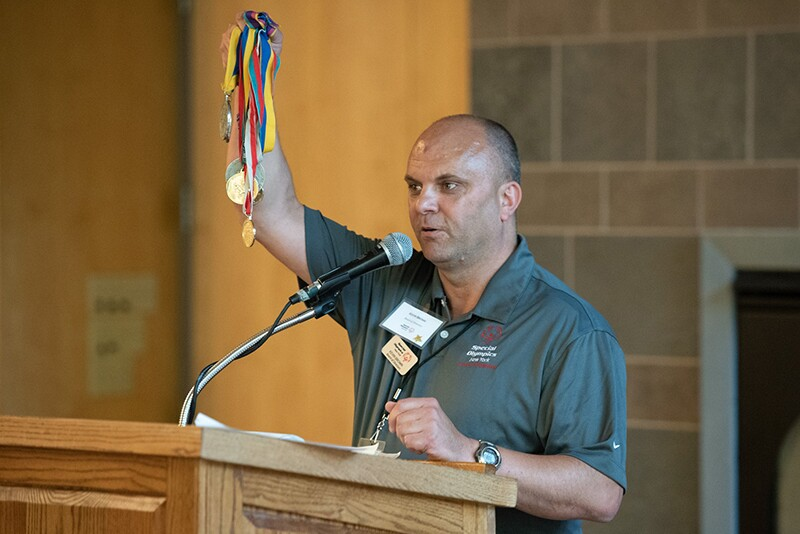 Kevin stands at a podium holding five medals up in the air and stares out to the audience.
