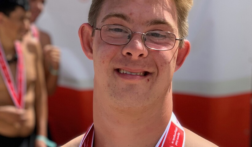 Chris Nikic proudly poses wearing three Special Olympics medals he won in swimming at a Special Olympics Florida competition.