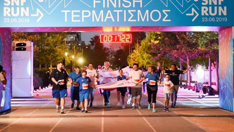 A group of people run towards the camera and across a finish line holding banners and waving their arms in the air.