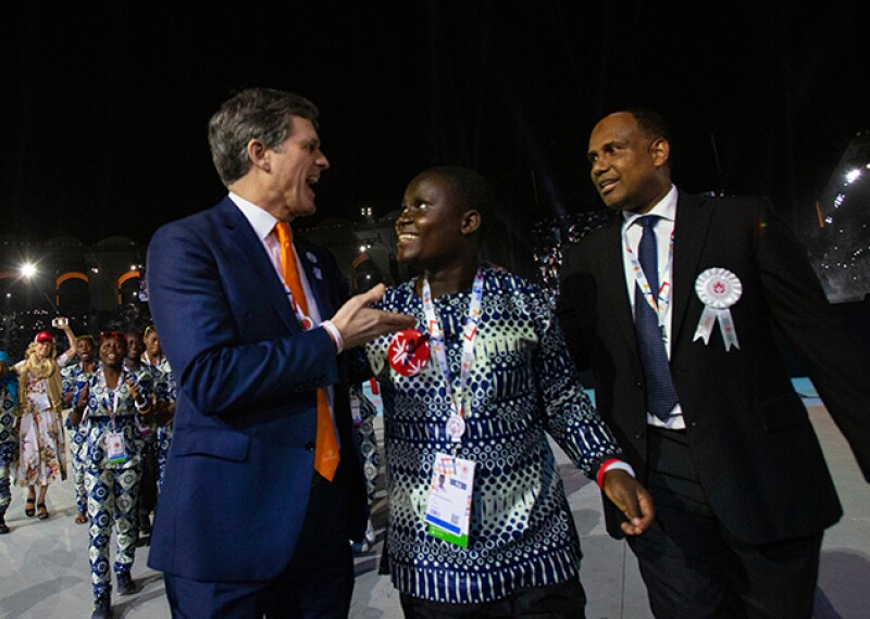 Malaki stands next to Tim Shriver and another Special Olympics representative as the delegation walks on stage at the World Summer Games.