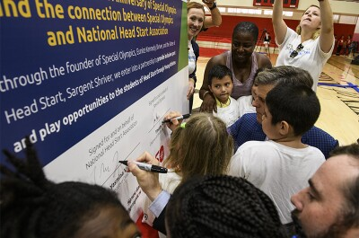 Dr. Timothy P. Shriver, Chairman of Special Olympics, on the right side and Thomas J. Sheridan, Senior Director of Government Affairs of the National Head Start Association, on the left side sign the large Memorandum of Understanding along with numerous young athletes.