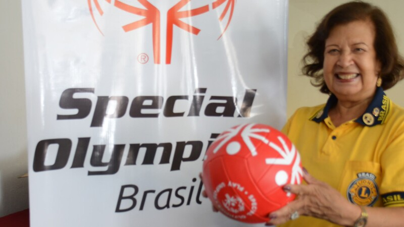Woman smiling and posing with a red football (soccer ball) standing next to Special Olympics Brazil signage.
