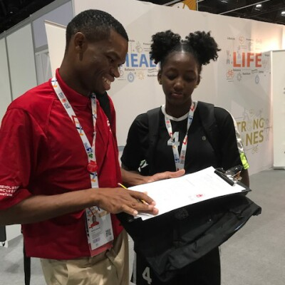 Male Health Messenger conducts a survey with a female athlete at an event.
