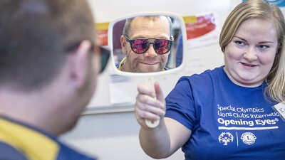 Athlete trying on ski glasses as a volunteer shows him his reflection in a handheld mirror.