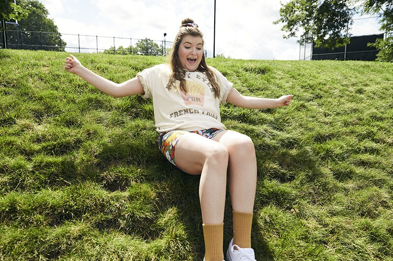 Kallie has fun sliding down a grassy hill in a t-shirt and biking shorts.