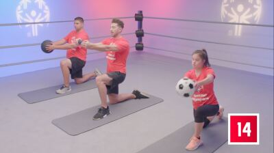 Two athletes and a trainer in a WWE ring performing balance exercises; all three are down on their left knee holding a weight in front of them.