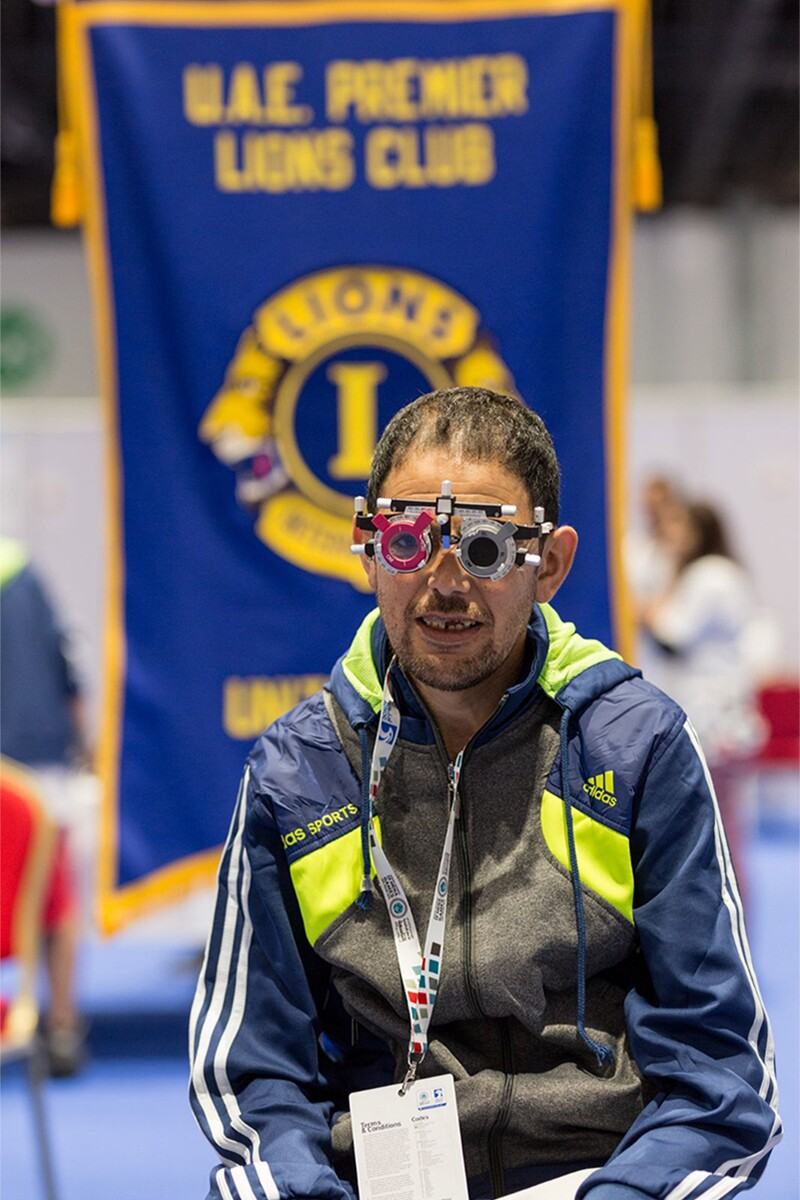 Athletes sitting with an ocular testing device over his face.
