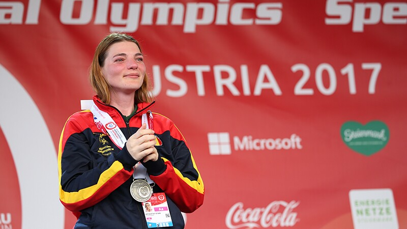 An athlete crying tears of joy with her medal draped around her neck.
