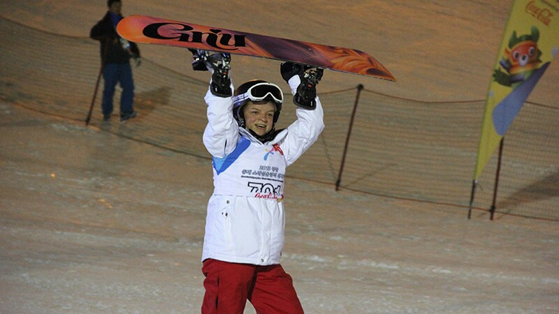 Special Olympics athlete Daina Shilts carries her snowboard up high, triumphant after a great day on the slopes.