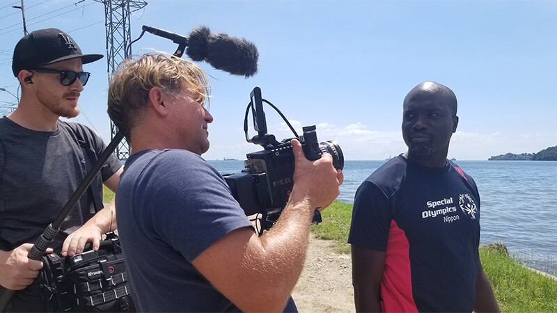 Kester being video recorded by a vidographer and boom mic operator. They are standing on a shoreline and water is in the background. Kester has on a Special Olympics Nippon black t-shirt.