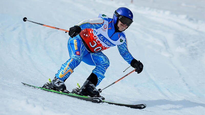 Special Olympics athlete wearing blue ski gear skis down a hill during an alpine skiing competition.