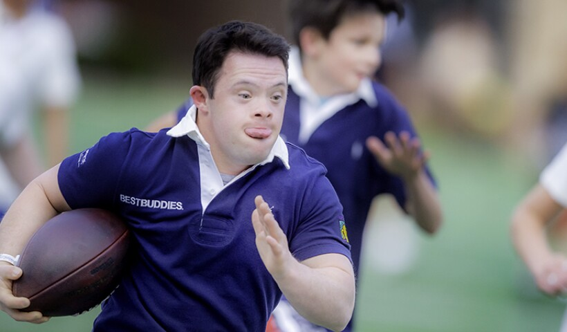 Young athlete running with an american football; he has on a purple best buddies polo. another athlete with the same polo can be seen in the background.