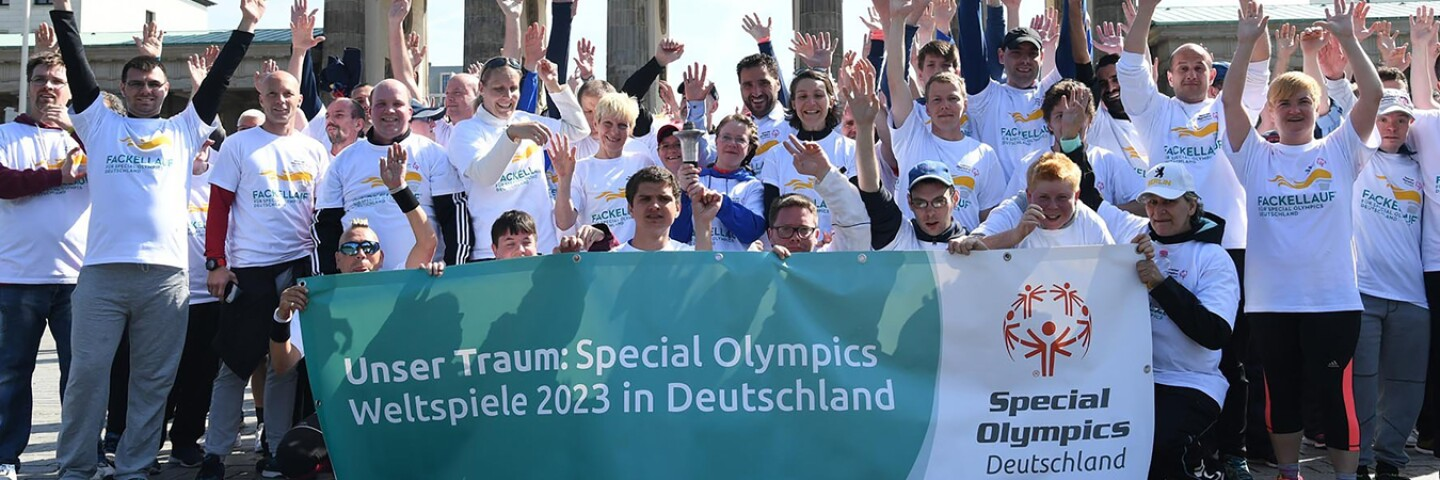 a large group of athletes and representatives cheering with their hands up and some are holding a banner in front of them.